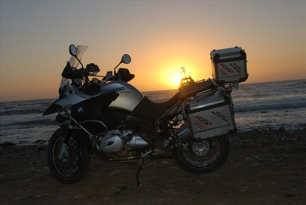 Motorbike beside the ocean while the sun is setting.
