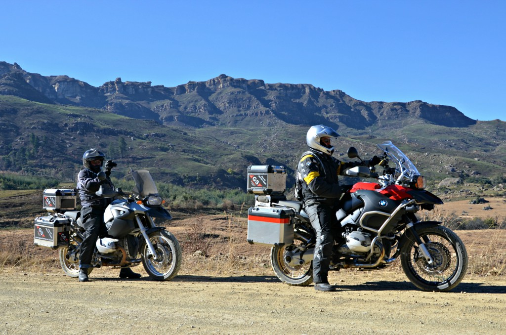 Two men on bikes, on the side of the open road, with the view of the mountain behind them.