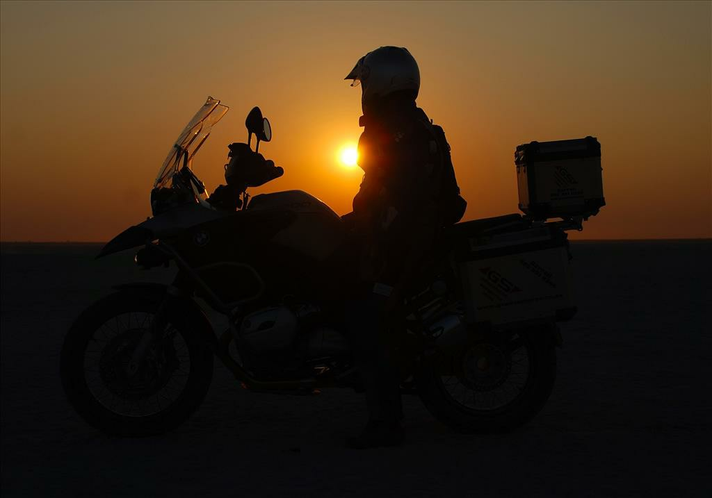 A man sitting on his motorbike while the sun is setting.