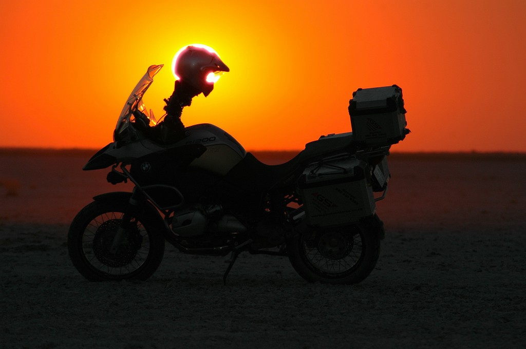 A motorbike standing in the desert while the sun is setting.