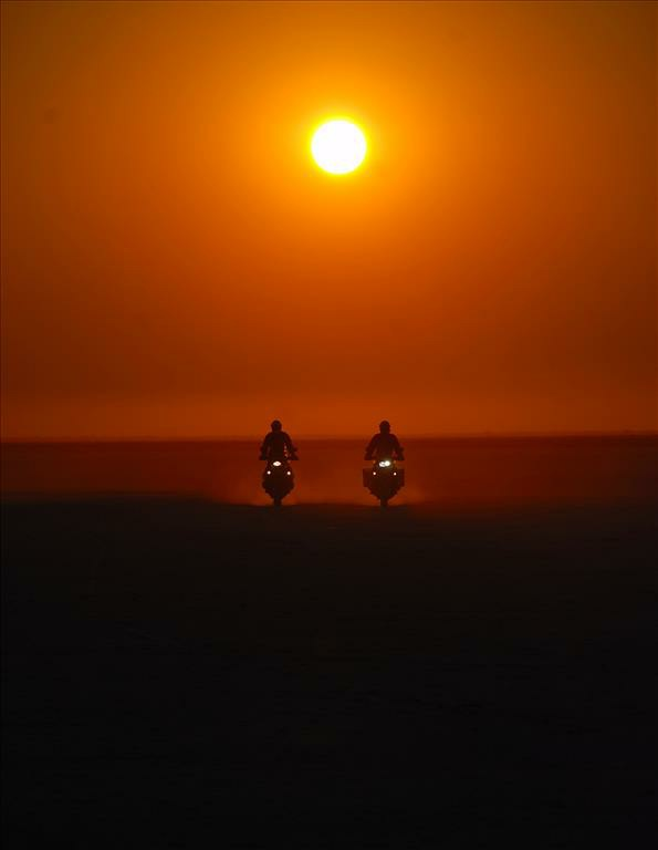 Two people riding on their motorbikes in the sunset.