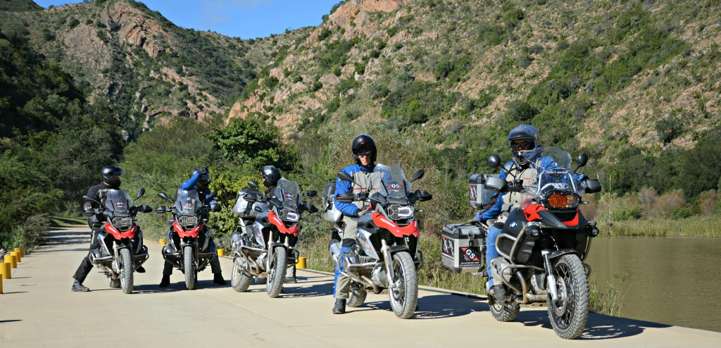 Five men on motorbikes. Not moving, on a mountain road.