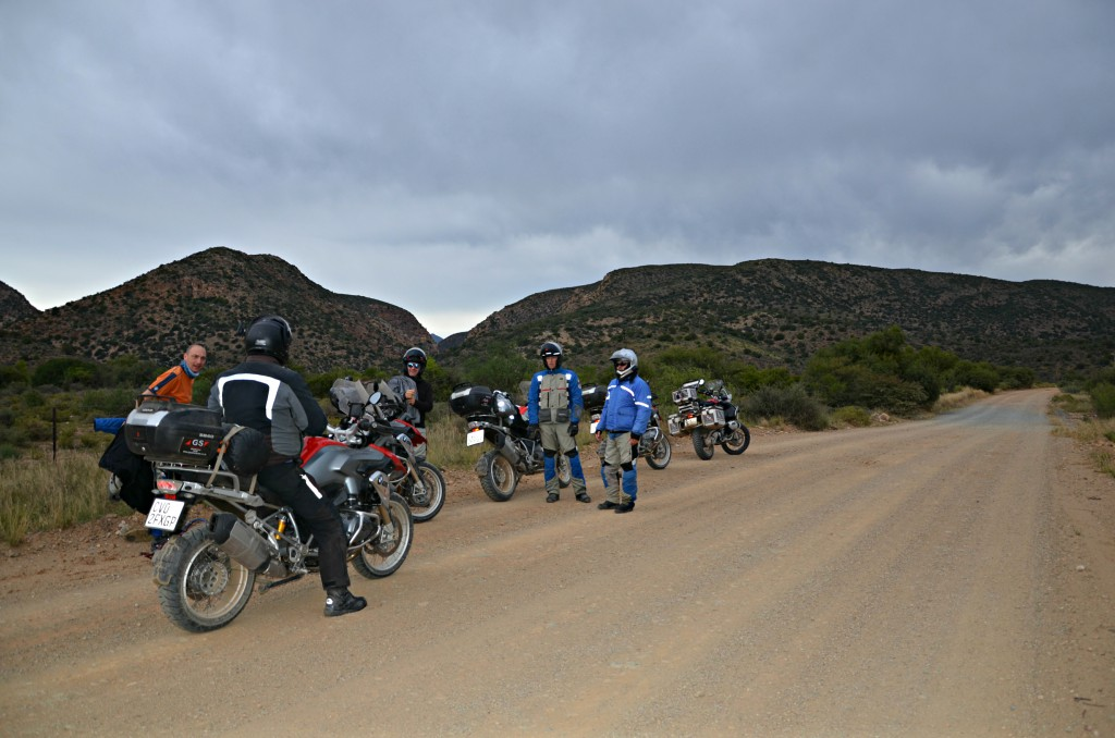Five men with motorbikes, four standing and one seated on a motorbike in the middle of a mountain road.