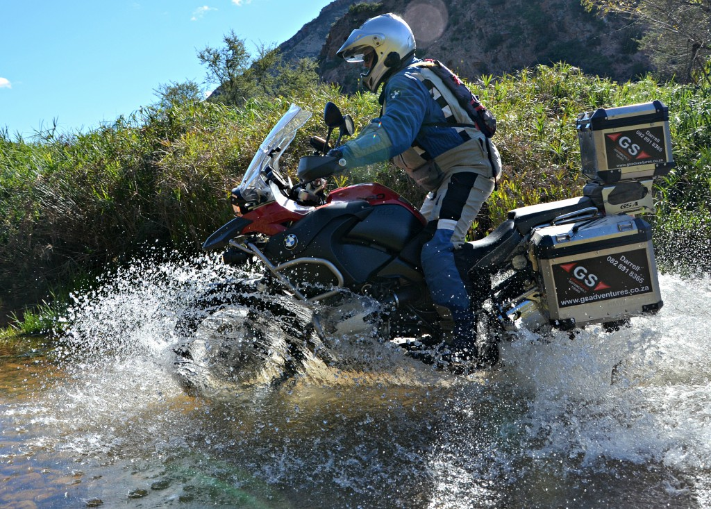 Man on motorbike riding on a mountain road filled with water.