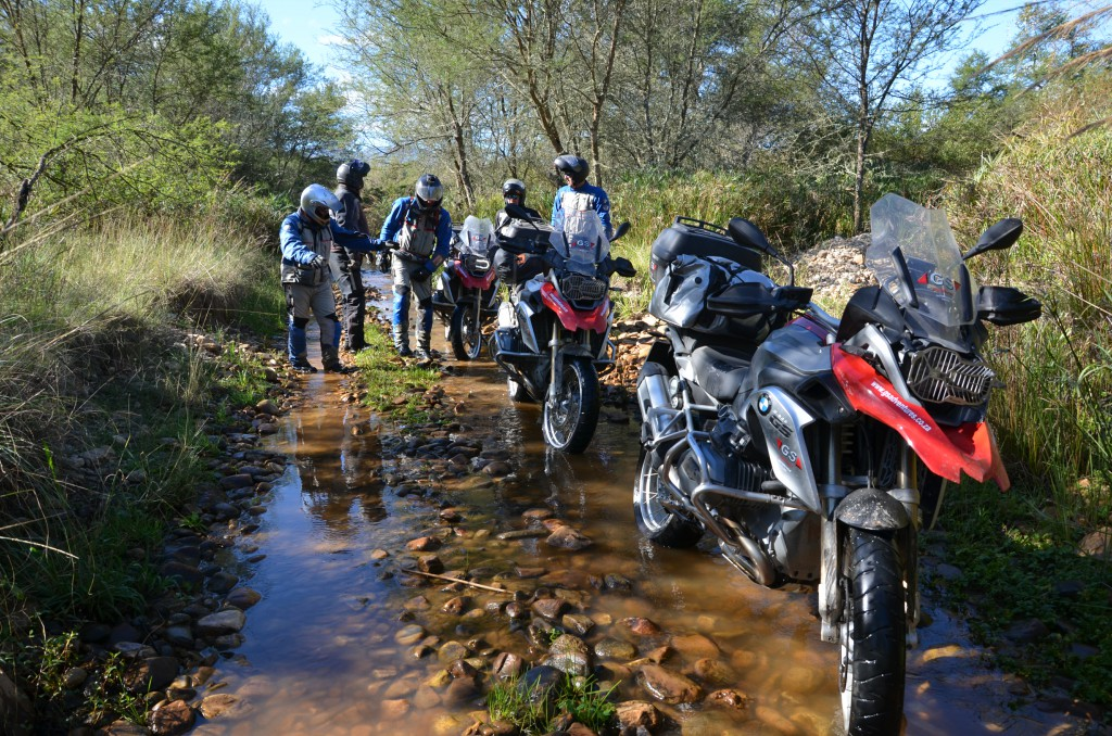 Five men with motorbikes standing almost beside each other. On a mountain road filled with water.