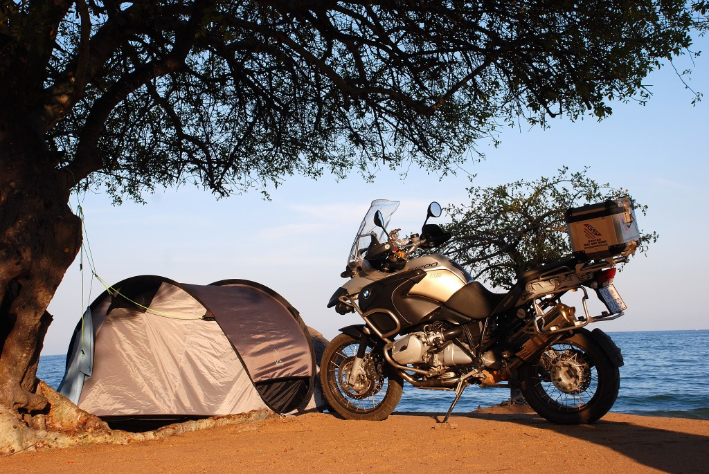 A motorbike besides a tent at a camping ground.