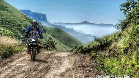 A rider riding his motorbike on a dirt road with misty mountains in the background.