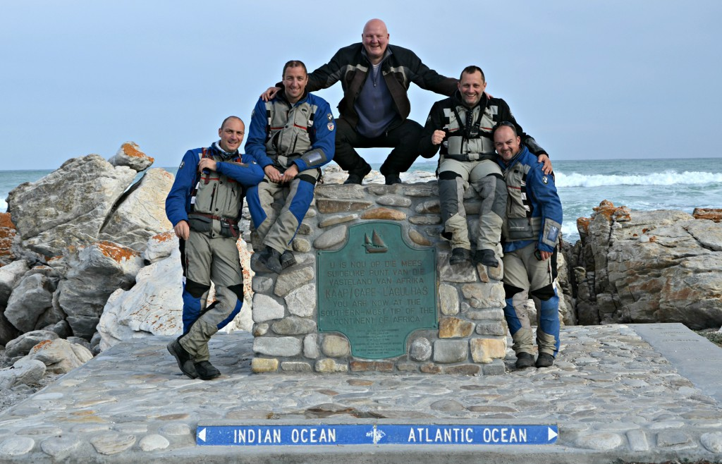 Five men sit on the rock where the Atlantic ocean and the Indian ocean meets each other.