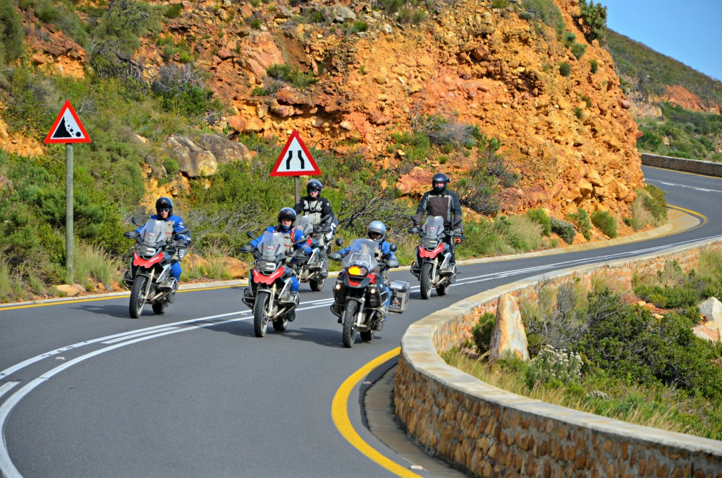 Five men on their motorbikes going uphill on an open road.
