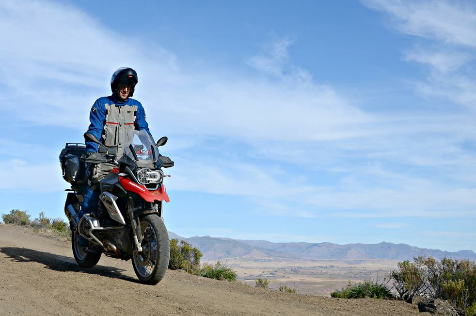 Man on motorbike going downhill on a dirt road.