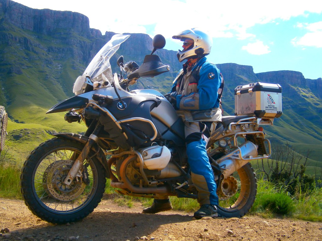 Man sitting on a motorbike with a mountain in the background.