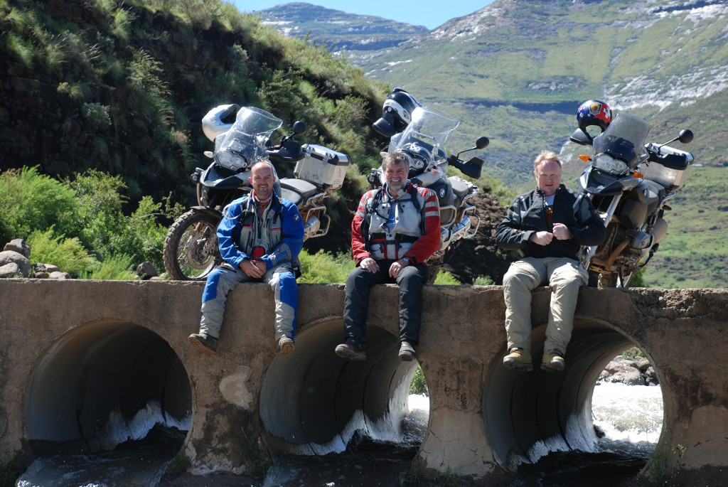 Three men sitting on a river bank with their motorbikes behind them.