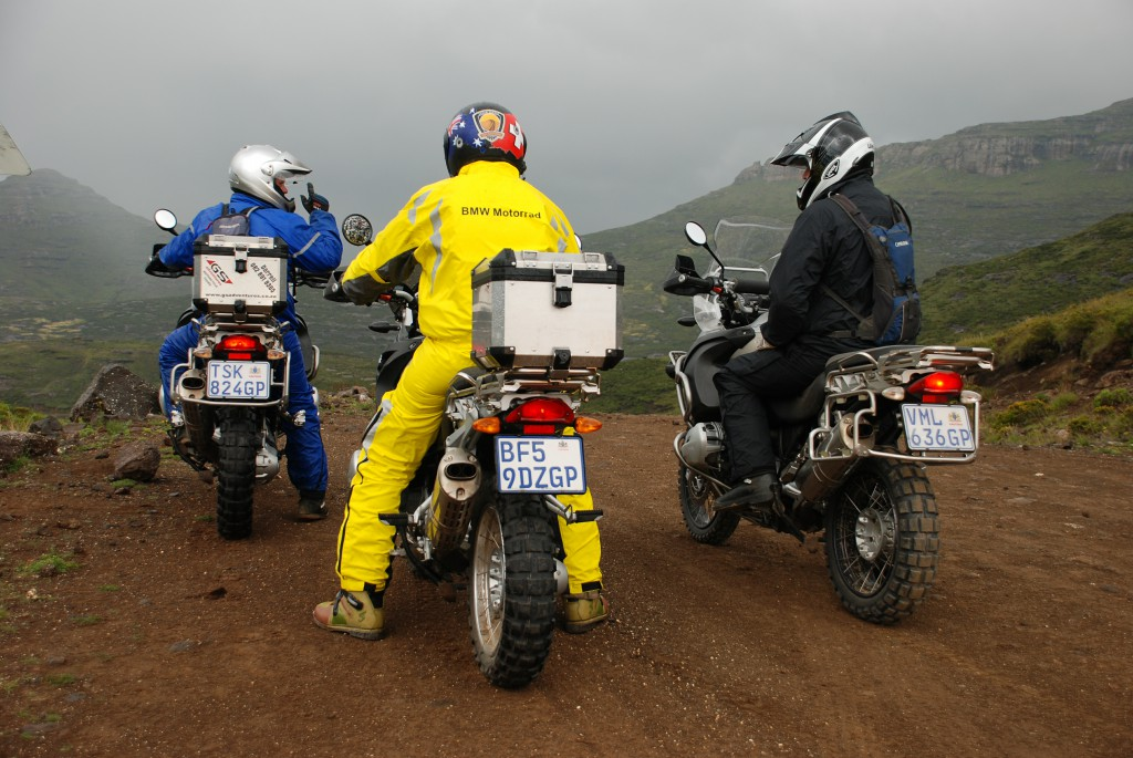 Three men sitting on their motorbikes, on a dirt road.