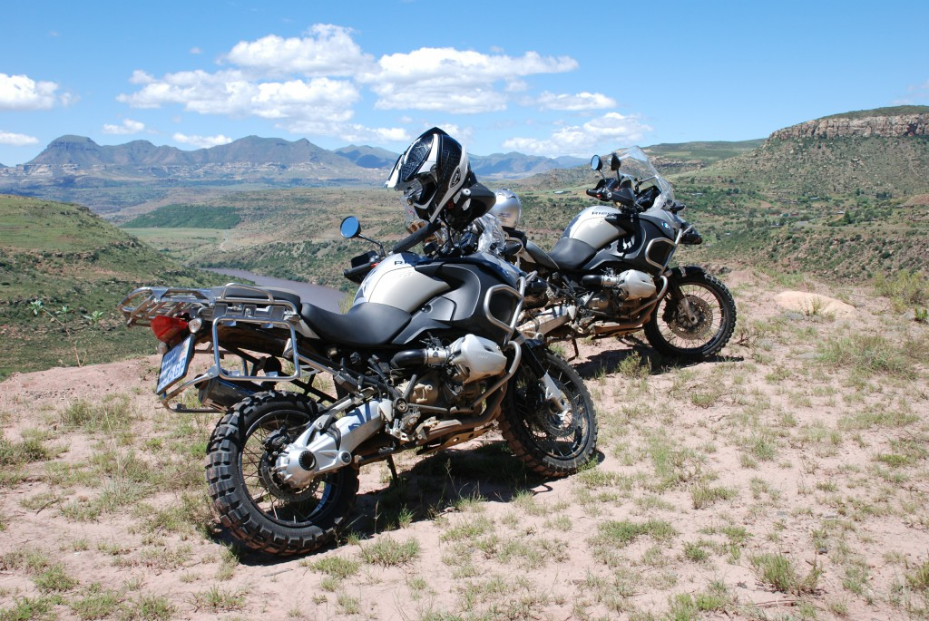 Two motorbikes standing in the mountains.