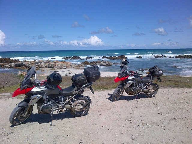 Motorbikes on a beach with the ocean in the background.