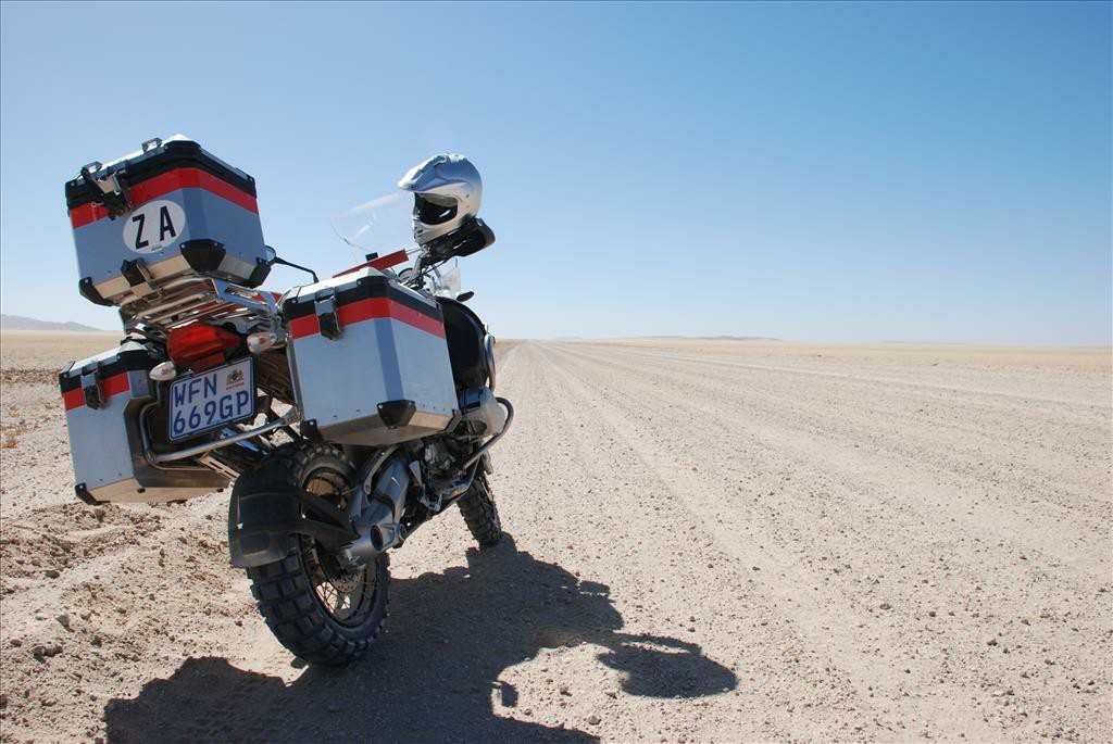 A close up of the back view of a motorbike on the side of a dirt road.