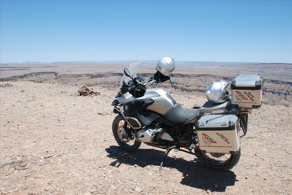 A close up of the back view of a motorbike on a dirt road looking out over a canyon.