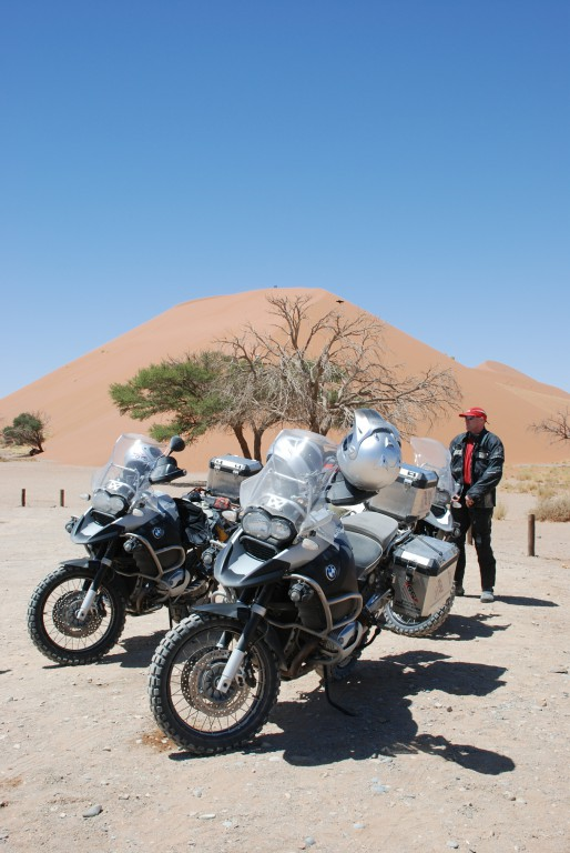 A group of motorbikes in the desert with a man beside them.