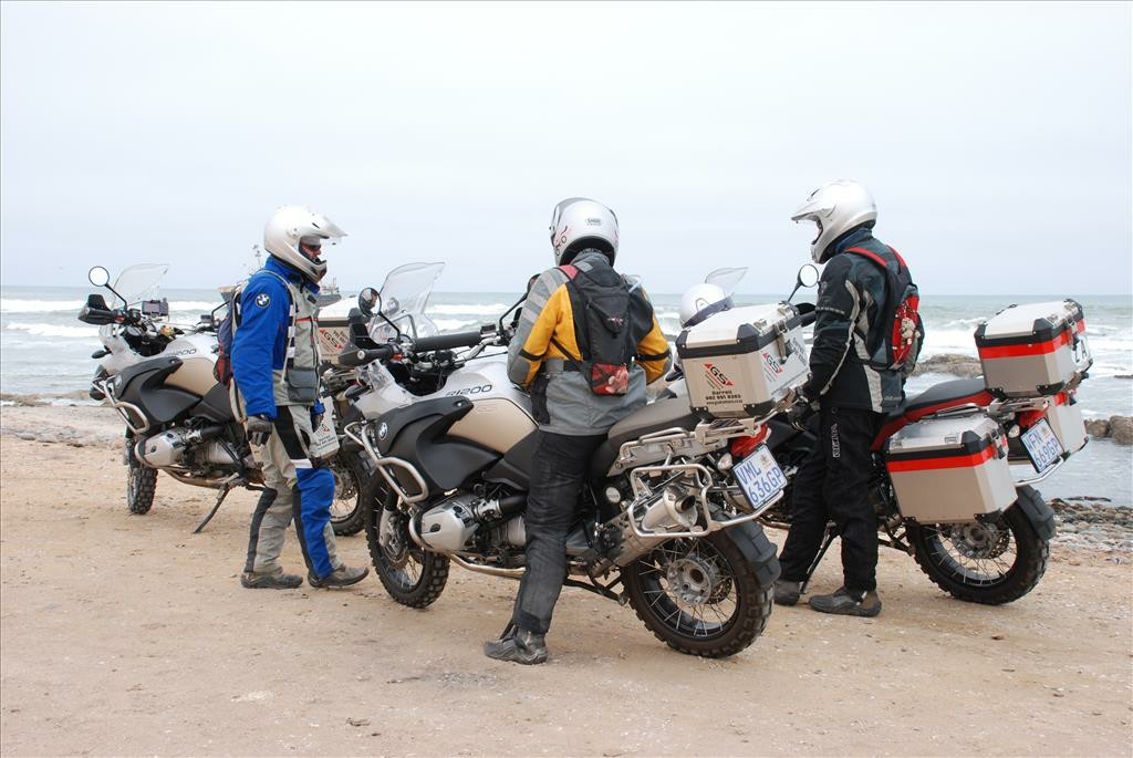 Three motorbikes, with the two drivers standing beside their motorbikes and the other driver on his motorbike.