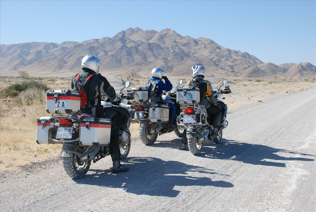 Three motorbikes riding on the side of a dirt road.